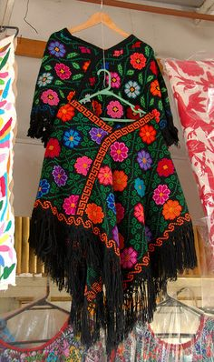These are examples of the ancient Mexican garment known as a quechquemitl, or closed-shoulder cape. The ones in this photo from the Ciudadela artesanias market in Mexico City were made in the Nahua region of Hueyapan, Puebla. More of a pixalated cross stitch style.