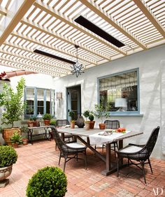 The terrace now serves as an alfresco dining room, featuring a teak table by Janus et Cie and Palecek chairs; the star pendant light is by Reborn Antiques.