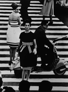 William Klein is an American photographer, painter film-maker, documentarian and graphic designer. This is a photograph by william klein taken in rome. He got two well dressed models with black and white dresses to cross over the zebra crossing whilst people and traffic started to pass by. People then noticed that it was staged and started to wonder if they should walk by or not. After the photo shoot men started too approach the girls because they thought were hookers.