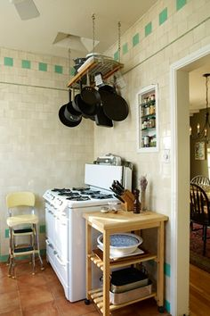 """A quick and simple improvement —bulky pots and pans hung overhead free up a ton of cabinet space and add to the visual charm of this working kitchen."