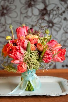 Garden style bouquet of ranunculus in shades of orange, yellow, burgundy and peach....hot pink Parrot Tulips....Jasmine Vine.....and Queens Anne Lace