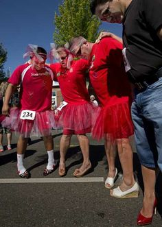 Hunter Mullins, l to r, Matt Ducatt, Mark Mullins, and Mason Seto show it's not so easy to balance on high heels before the Puyallup Walk a Mile in Her Shoes event to raise awareness/money for sexual assault/domestic violence awareness at the Meeker Days Festival on Saturday, June 22, 2013. Lui Kit Wong/Staff photographer LUI KIT WONG — The News Tribune