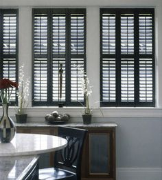 dark wood plantation shutters with a blue colored wall, white molding