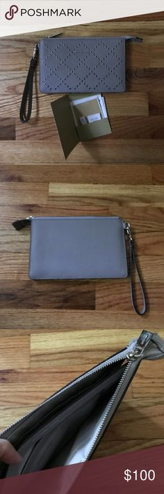 Michael Kors Daniela Pearl Gray Wristlet Michael Kors Daniela Wristlet. Pearl Gray with grommets. Silver hardware. Brand new! Was the display at the store but I never actually used this wristlet. Comes with care booklet and tag. Fits an iPhone 7plus inside! Zipper opens to one inner pocket with a middle divider. One side has 6 card slots and the other has a patch pocket. Michael Kors Bags Clutches & Wristlets