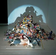 you can see 2 shadow men over the garbage mountain : created by Tim Noble & Sue Webster