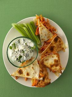 Buffalo-Chicken Quesadillas    1 store-bought rotisserie chicken, shredded   ¾ c. buffalo sauce (available in a jar at the grocery store)   1½ c. shredded Monterey Jack cheese   12 soft flour tortillas (taco size)   Nonstick cooking spray   Blue-cheese dressing   Celery sticks
