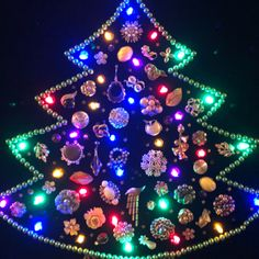 Tree made out of baubles, trinkets, and jewelry with Christmas lights in frame.