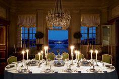 Champ de Bataille | Jacques Garcia: la table de la salle à manger d'apparat ornée d'argenterie lors d'une soirée d'été; le bonheur d'être à l'intérieur comme dehors.