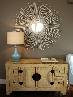 buy a cheap round mirror and hot glue dowel rods to back of mirror (spray paint rods any color you want) - incredible!