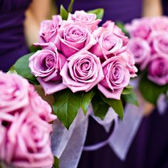 Bright roses complement the bridesmaids' deep purple gowns.Photo Credit: Kimberly Chau Photography
