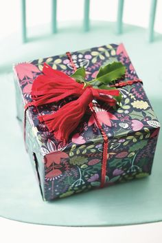 Wrap up your Christmas gifts in pretty decorative boxes with a classic red bow.