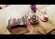 """""""We are All Mad Hear""""  The Mad Hatter Quote   Accented with the Tea-Cup and a flower from the garden    The necklace is 24"""" silver plated Ball chin. Great Length.  Comes ready for Gifting or keep for your self.     I am a Big Alice fan and get so excited when i am adding to her collection. I hope..."""