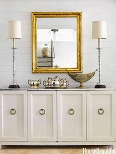 White console with gold framed mirror, buffet lamps & silver.