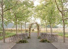 Beaulieu Garden ceremony. Vineyard ceremony. Tree lined path wedding ceremony. Cherry blossom wedding ceremony. Jasmine vine wedding ceremony. Wrought iron cafe chairs for a wedding ceremony. Northern California wedding venues. Romantic wedding venues in napa valley.