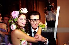 Franch model Laetitia Casta, with flowers in her hair, hugs French fashion designer Yves Saint Laurent at Yves Saint Laurent Fashion Show 2000…