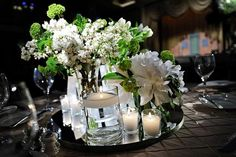 Tiered centerpiece.  Candles. Peonies, viburnum, lilac blooms.  Pretty.
