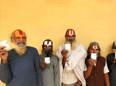 Holy men display their voter identification cards as they stand in a queue to cast their votes