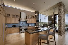 """""""We combined some traditional and contemporary touches in the kitchen."""" White oak Shaker-style cabinets and brown schist stone lend a warm, contemporary feel. Behind the range wall, you can see how the roof floats, providing clerestory windows that let in additional daylight."""