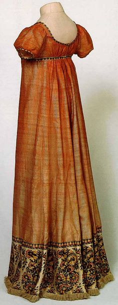 Photograph of French dress of red net with high waist, puff sleeves, and Kashmir-inspired motif at the hem, in the posession of the Musée Historique de Tissu de Lyon