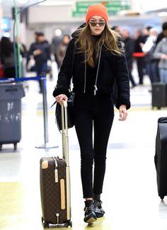 Gigi Hadid wearing Mansur Gavriel Lady Bag, Louis Vuitton Horizon Rolling Suitcase and AllSaints Asher Shearling Biker Jacket
