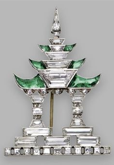An Art Deco diamond and emerald Pagoda brooch, Janesich, circa 1925. Designed as a pagoda with stylised columns and upturned eaves, set with baguette, square-shaped, trapeze-cut, triangular-shaped, single-cut and rose-cut diamonds, accented with 6 calibré-cut buff-top emeralds, mounted in platinum, signed JANESICH, numbered. #Janesich #ArtDeco #brooch