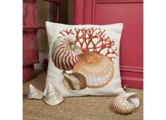 Coussin clair avec des motifs de coquillages sur fond de corail.