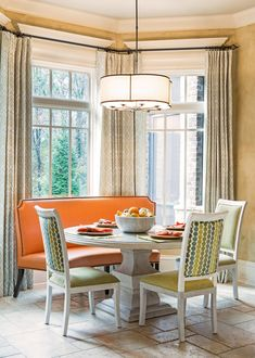 A breakfast area with a bright orange banquette | archdigest.com