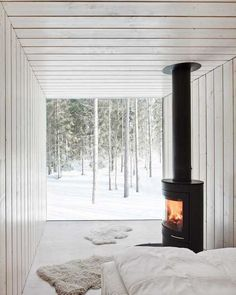 snow, window as a wall overlooking the forest, a wood stove in the bedroom