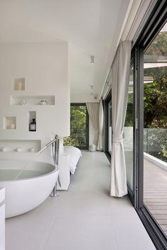 森に向かって開く4階建での開放的なリノベーションハウスのバスルームとベランダ
