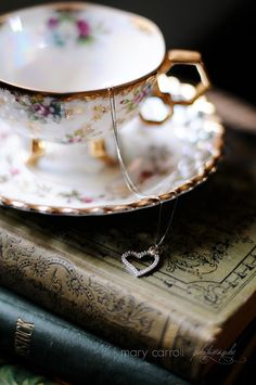 Heart necklace, tea cup and books