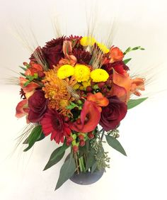 Rich fall tones in a clutch bouquet designed by Sunnycrest Flowers. Wheat, calla lilies, roses, hypericum berries,gerbera, roses, poms, seeded eucalyptus, and other flowers add lovely texture. #fallweddingflowers  #richtexture  #callalilies