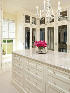 Has the key elements of a fabulous closet: center marble top island, chandelier, window...just needs color & to personalize