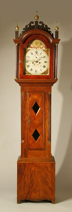 """A fine country Hepplewhite tall clock with scrolled fretwork, reeded plinths, hood columns and quarter columns on case, double-glassed case door, and cut out base. Figured birch, in original surface. Painted and gilded dial with urn and shell decoration. Eight day works, southeastern NH, probably by Kennard, Newmarket, c.1815. Exceptional condition, with only a very small repair to one scroll on the fret. 89"""" ht. From the Atwood family of Tilton, NH."""