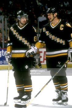 Jaromir Jagr #68 and Mario Lemieux #66 of the Pittsburgh Penguins talk during a hockey game against the Washington Capitals on December 26, 1993 at USAir Arena in Landover, Maryland. The Capitals won 7-3.