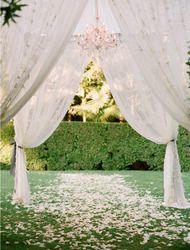 Using the frame of a pop-up canopy, dress with tulle, lace & light, if there is any available outlets.