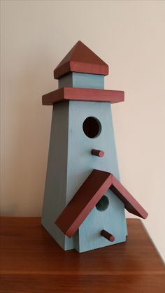 Vintage lighthouse-shaped bird house, painted with two tones of chalk and mineral paint, with copper paint on the roofs.