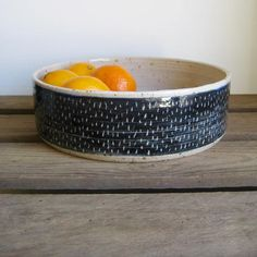 A lovely modern style fruit bowl. This bowl is handthrown in a natural speckle stoneware clay. The outside is decorated using a deep blue slip. Then a textured pattern of vertical lines has been scratched through to reveal the bare clay underneath - a technique called sgraffito. The