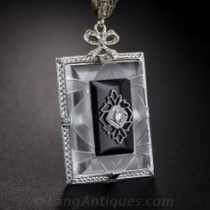 Art Deco Quartz Crystal, Onyx and Diamond Pendant. This delightful and feminine 1930s depression-era pendant features a central rectangular plaque of carved quartz crystal in an embossed white gold frame, inlaid with onyx and pierced in the center with a sparkling European-cut diamond. Topped with a sweet bow and lacy white gold filigree loop, this special and unusual pendant measures 1 9/16 inches long and 3/4 inch wide and is suspended from a 16 inch white gold cable chain.