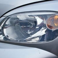 Dust and oxidation build-up from driving can leave your headlight lenses looking foggy. Foggy headlights can impair your driving by dimming lighting and cutting down the range of your headlights. There are a number of expensive ways to clean the film and fog from your headlight lenses, but you can also clean your headlights at home using...