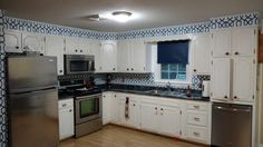 A beautiful kitchen makeover using our Navy Grand Trellis peel and stick NuWallpaper!
