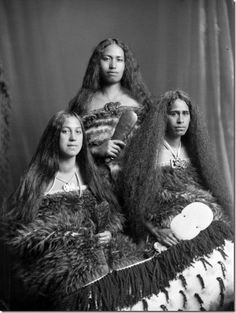 Mrs J A Jury and two other women, who are possibly kin to Mrs jury in some way; the women have combed their long hair out, are wearing traditional Maori kiwi cloaks and tiki (greenstone ornaments), and holding traditional weapons. Taken by Frank J Denton in 1908.