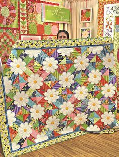 daiseys.  Numerous reasons why I love this quilt, 1. the scrapiness of the background, could virtually use any colors.  2.  the use of the background fabric more than once, it is almost demanding that you find another piece of the fabric somewhere else in the quilt.  3.  the daisies, of course, give your eye a bit of a rest.