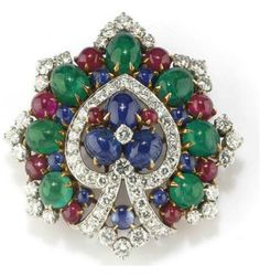 CLIP IN DIAMONDS AND STONES COLOR CABOCHON SIGNED BULGARI. a leaf design with a central motif in diamonds, sapphires and rubies cabochon, framed in emeralds, rubies, cabochon sapphires and diamonds, French Punch gold, circa 1970