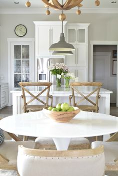 White kitchen with rustic wood furniture accents, tulip table