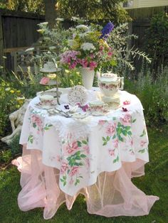 Vintage meets outdoors and girlie! A vintage Wilendur floral tablecloth tops a tulle or organza undercloth. Very nice against the al fresco green backyard setting for a tea or special breakfast with friends.