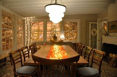 Dining room design—Exposed ceiling beams, traditional brick flooring and warm wooden elements work together to fill the dining room with character and warmth. To bring the outdoors in further, production designer Beth Rubino wrapped logs in twinkle lights. Love the coopers- table Christmas decor