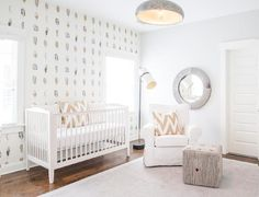 White and tan nursery features a white roll arm slipcovered glider adorned with a tan chevron pillow in Quadrille Tashkent Tan on Oyster fabric under a round gray hide mirror, Jamie Young Co.