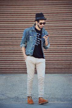 Comprar ropa de este look:  https://lookastic.es/moda-hombre/looks/chaqueta-vaquera-camiseta-con-cuello-barco-pantalon-chino-botas-safari-sombrero/1050  — Camiseta con Cuello Barco Estampada Negra y Blanca  — Chaqueta Vaquera Azul  — Pantalón Chino Beige  — Botas Safari de Ante Tabaco  — Sombrero Negro