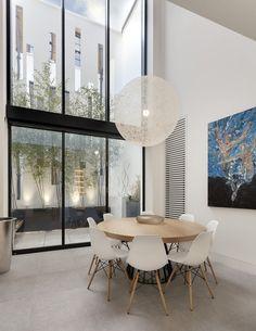 Der Speisesaal ist in weiß und hellen Farben, die positiv in das natürliche Licht von der massiven, volle Höhe Windows bereitgestellten glühend gewickelt. Eine minimalistische natürliche Holztisch steht umgeben von midcentury modern Stühle unter eine große, transparente kugelförmige Kronleuchter.