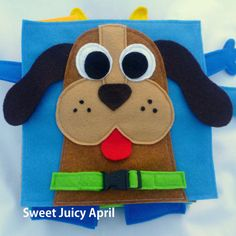 Dog collar buckle page. A dog face with a felt collar that buckles around the neck. Dog has long, flappy ears that hang off the page. This is a